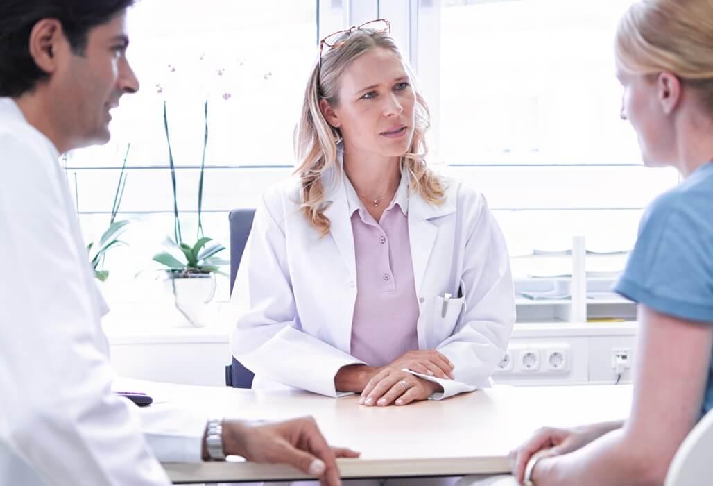 Eine Ärztin berät ein Ehepaar.