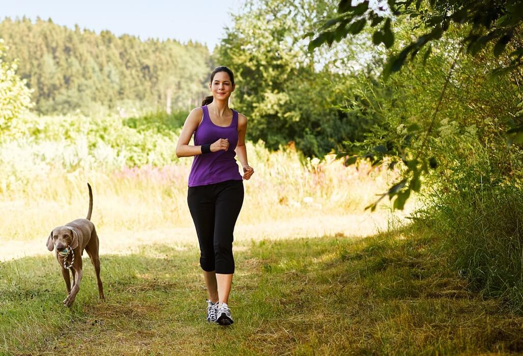 Junge Frau joggt mit einem Hund im Park.