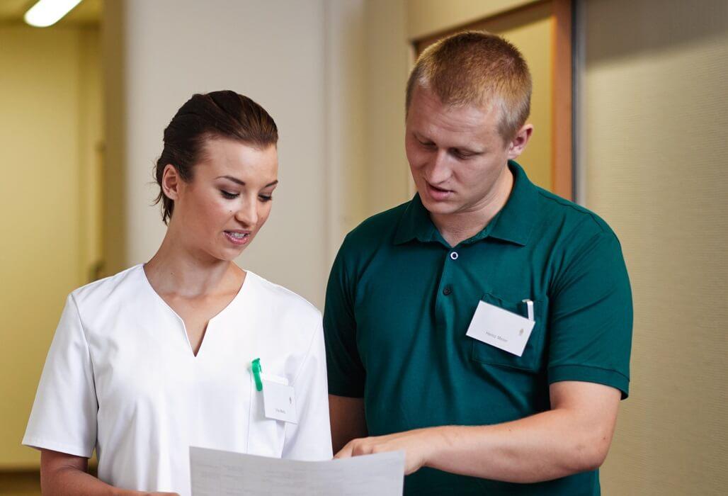 Eine Krankenschwester und ein Pfleger unterhalten sich.