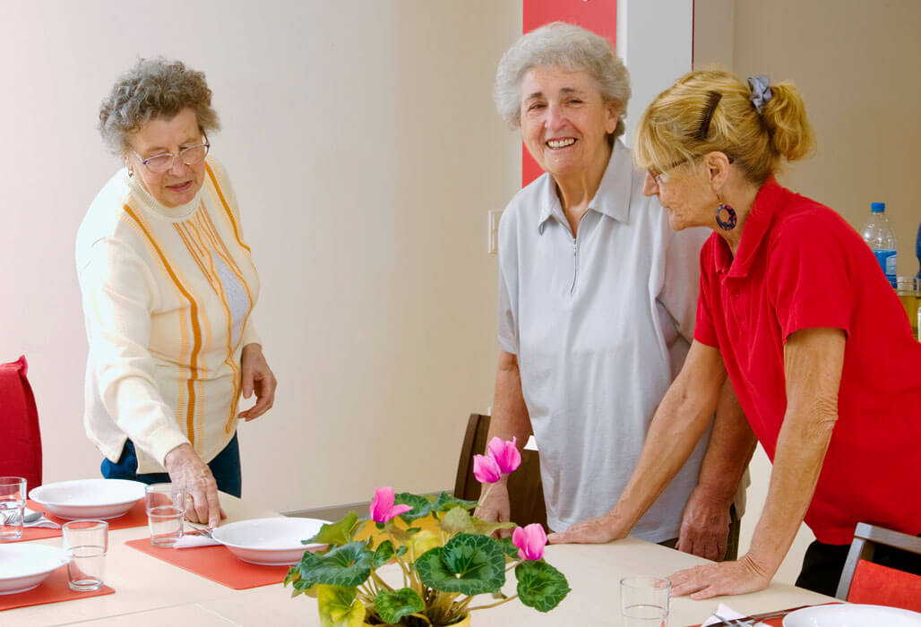 Zwei ältere Damen decken mit einer Pflegerin den Esstisch. Foto: Stefan Ernst