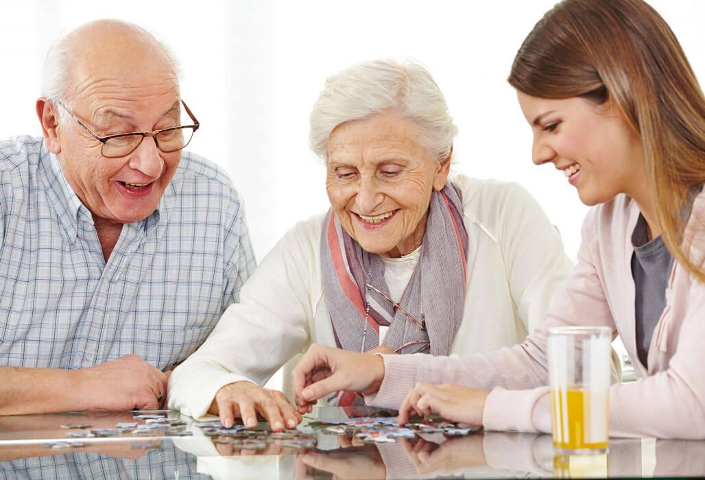 Ein älteres Ehepaar setzt mit Enkelin ein Puzzle zusammen.
