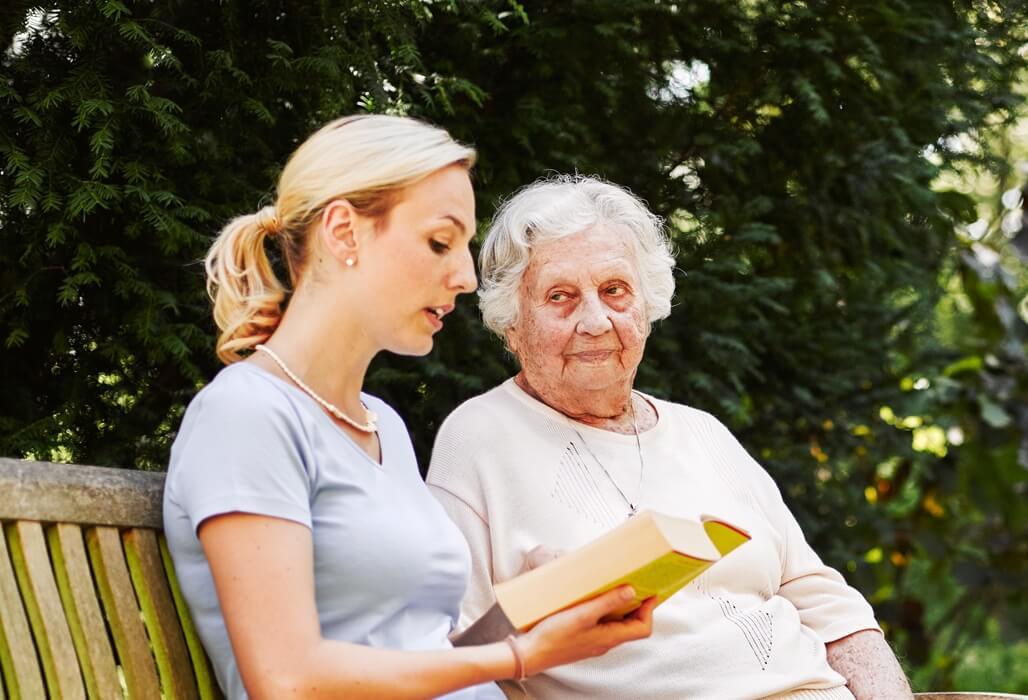 Ehrenamtliche Helfering liest einer älteren Dame etwas vor.
