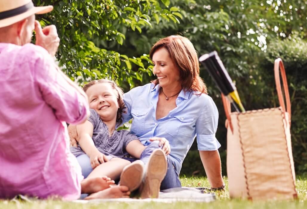Elternund Kind sitzen auf einer Decke im Park.