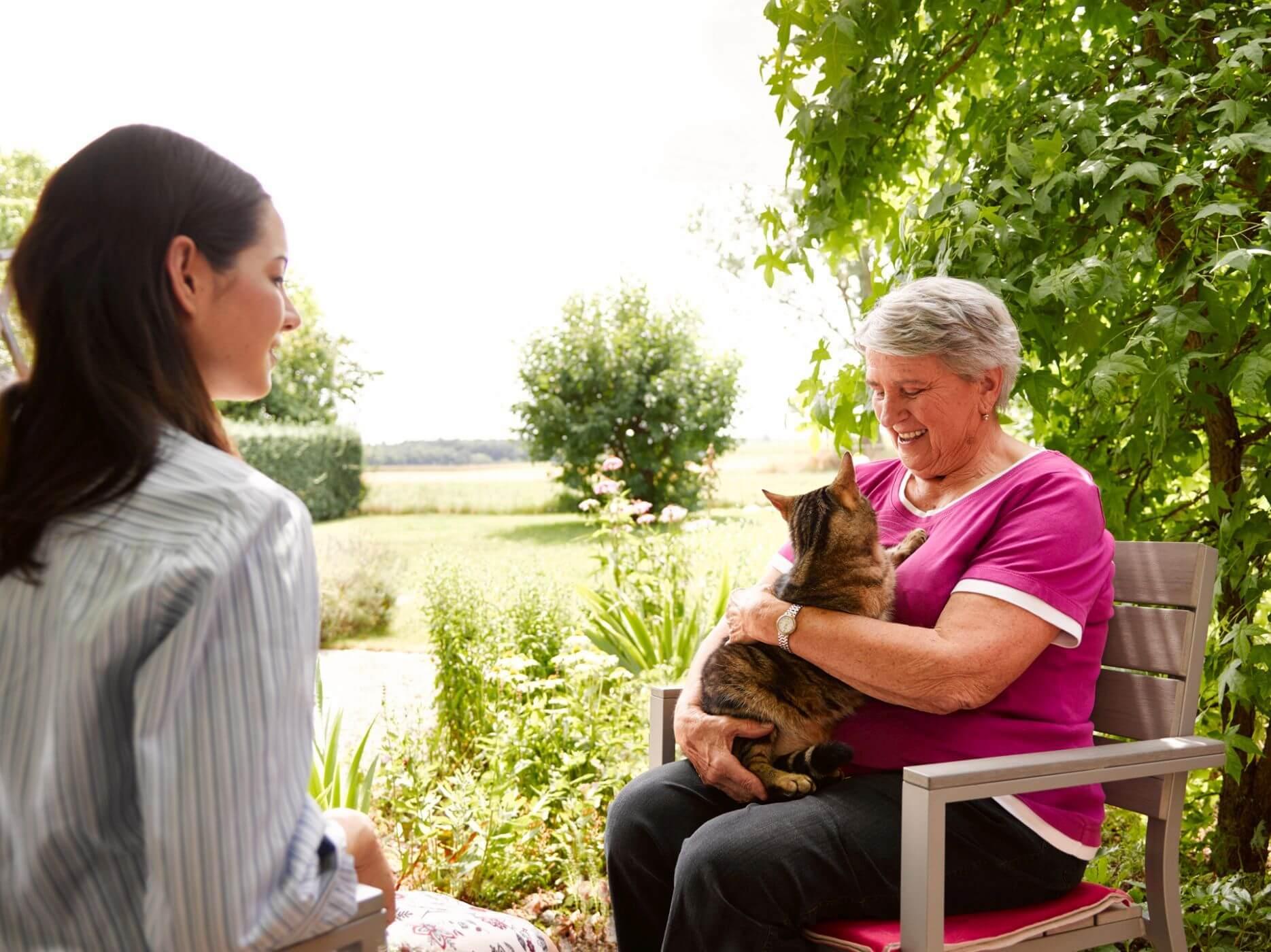 Ältere Dame sitzt mit Enkelin und ihrer Katze im Garten