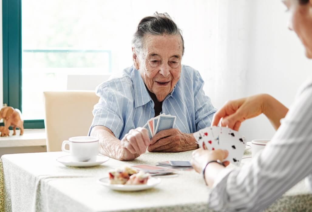 Ältere Dame beim Karten Spielen.
