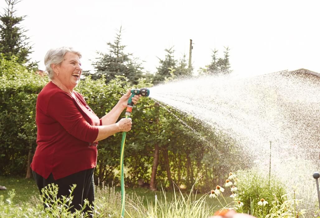 Ältere Dame bewässert den Garten.