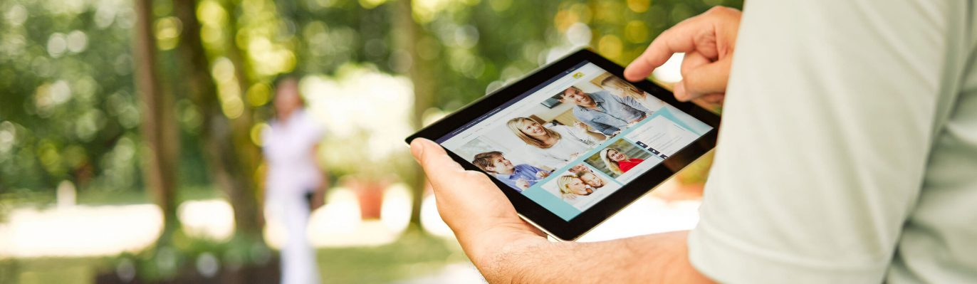 Ein Mann surft mit einem Tablet auf der Internetseite des Bayerischen Staatsministeriums für Gesundheit und Pflege