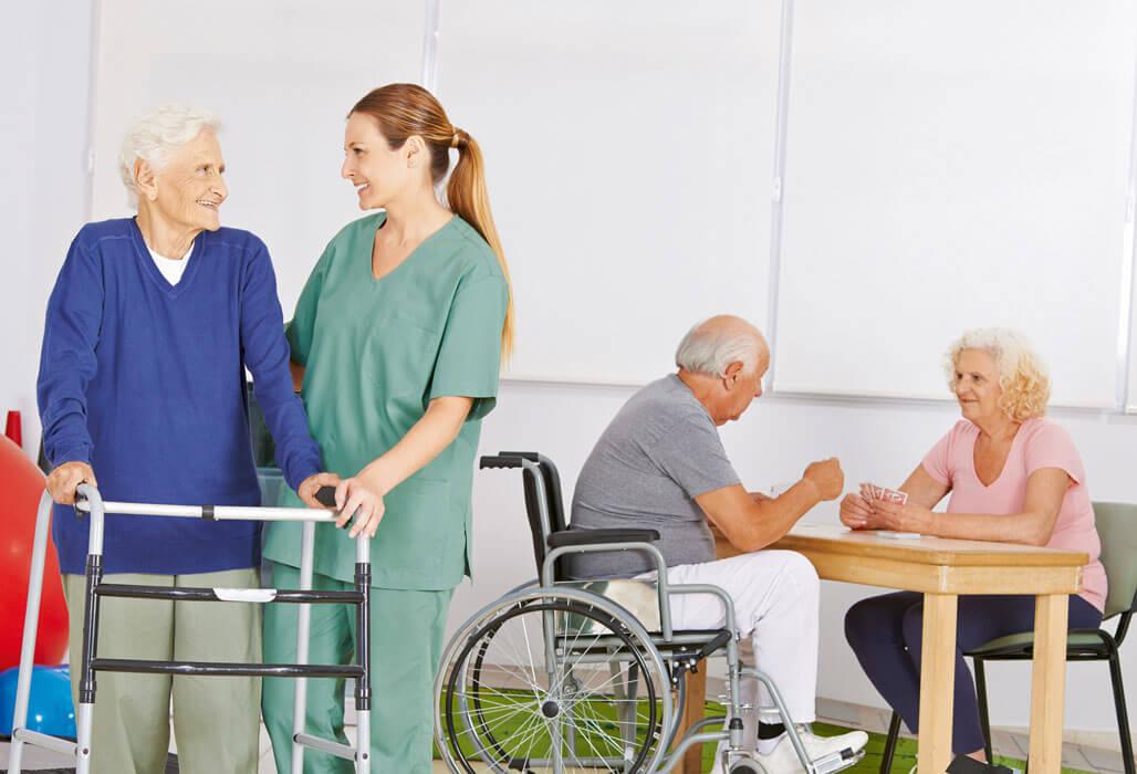 Pflegerin hilft älterer Dame an der Gehhilfe. Mann im Rollstuhl spielt mit einer Frau Karten.