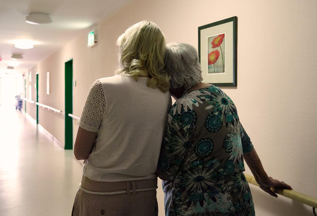 Ältere Dame lehnt sich an ihre Enkelin