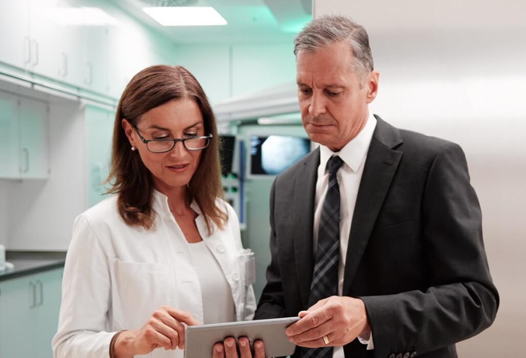 Eine Ärztin und ein Krankenhausbetreiber gehen gemeinsam ein Dokument durch.