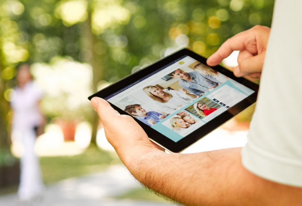Mann hält ein Tablet in der Hand und recherchiert auf der Internetseite des StMGP.