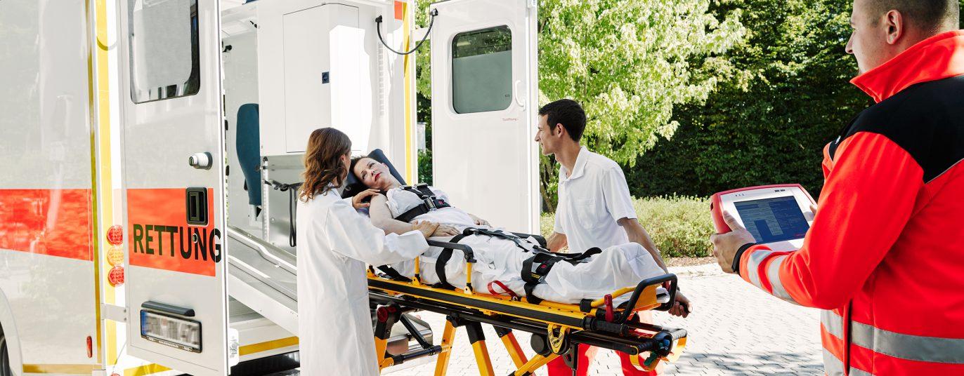 Patientin wird von Sanitätern in den Rettungswagen geschoben.