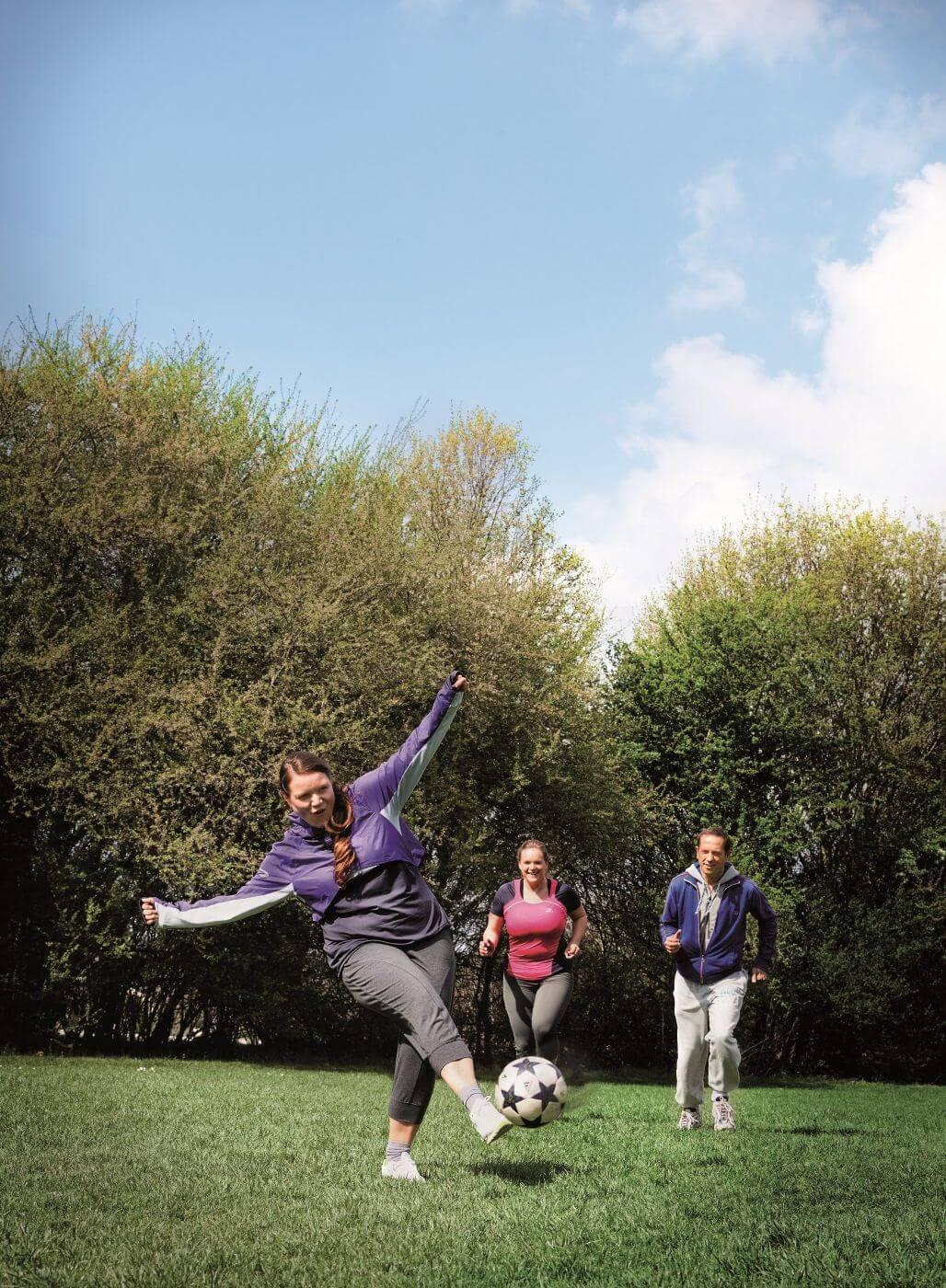Drei Freunde spielen Fußball im Park.