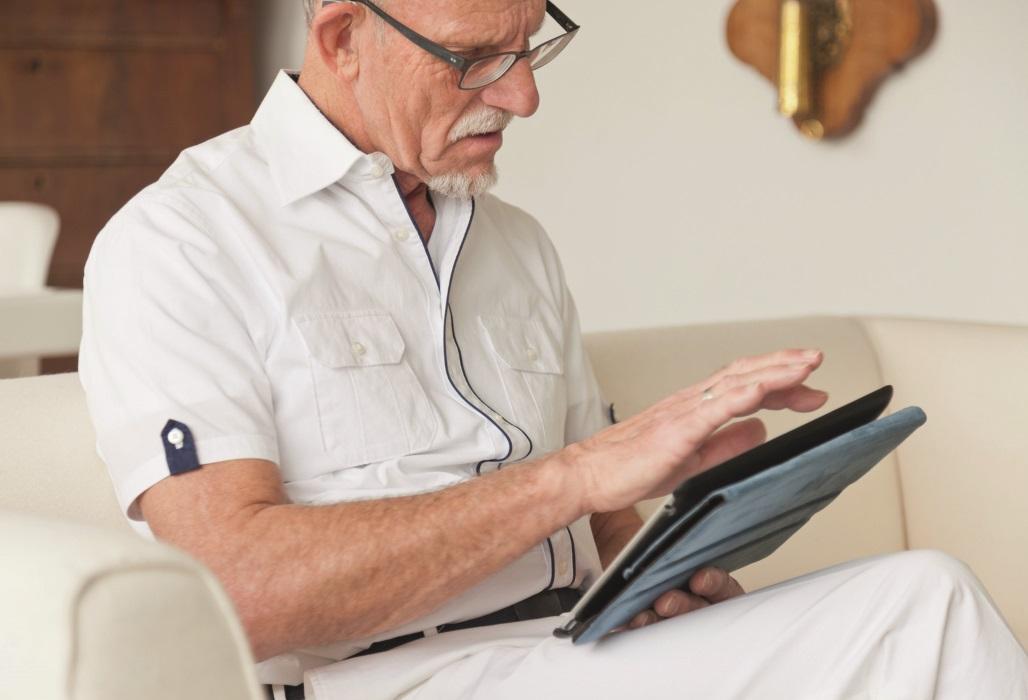 Mann recherchiert auf seinem Tablet nach Ärzten.