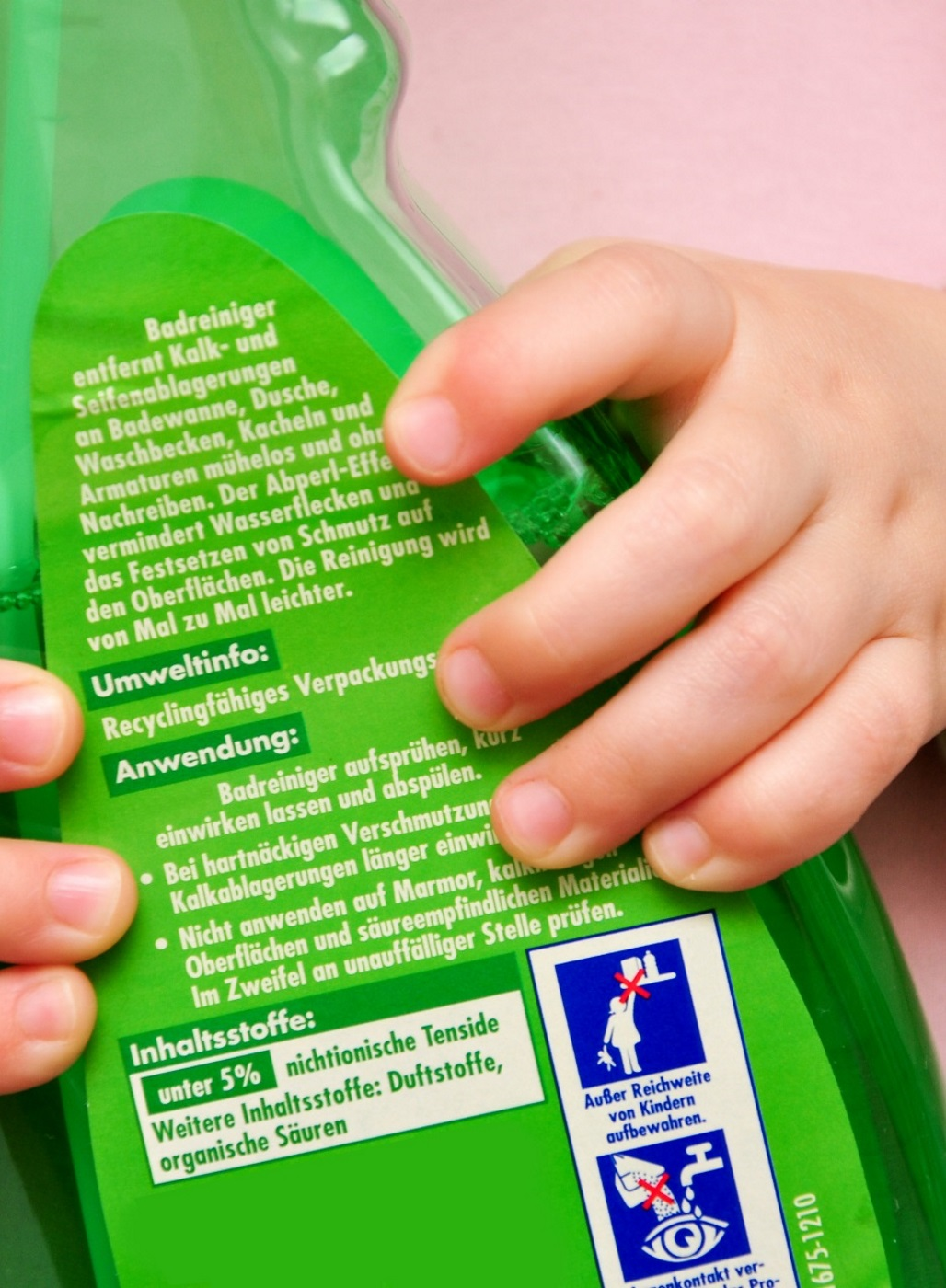 Kind hält einen Badreiniger in der Hand.