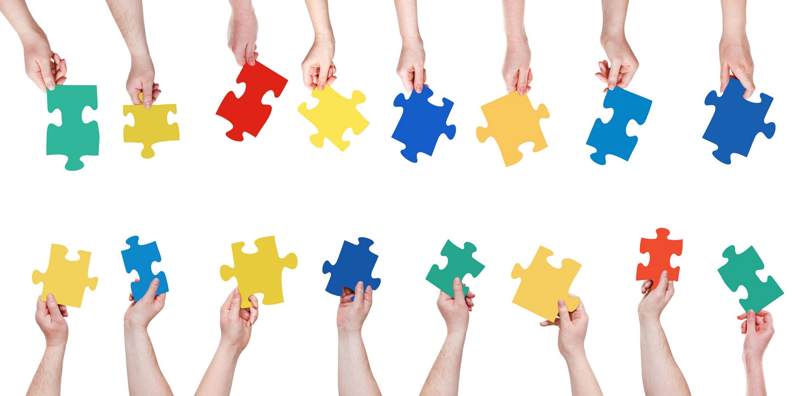 Viele Hände führen Puzzleteile zusammen.