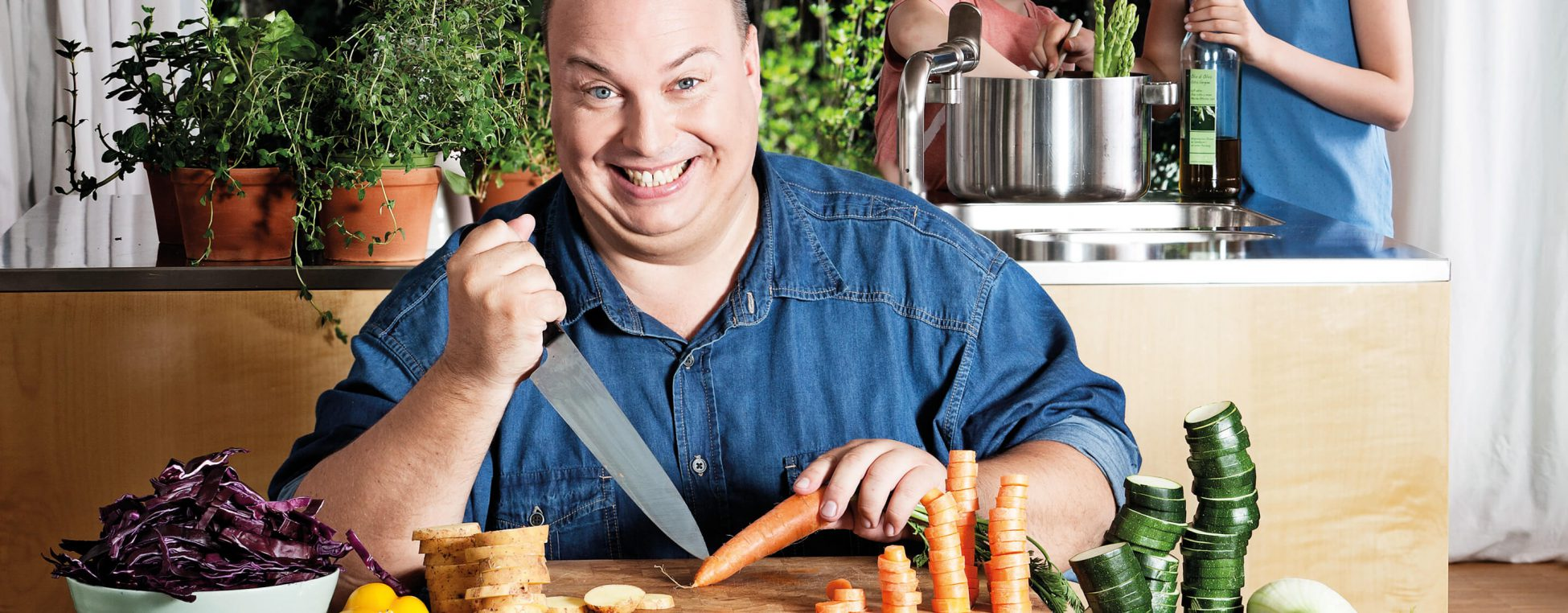 Korpulenter Mann mit Messer und Gemüse.