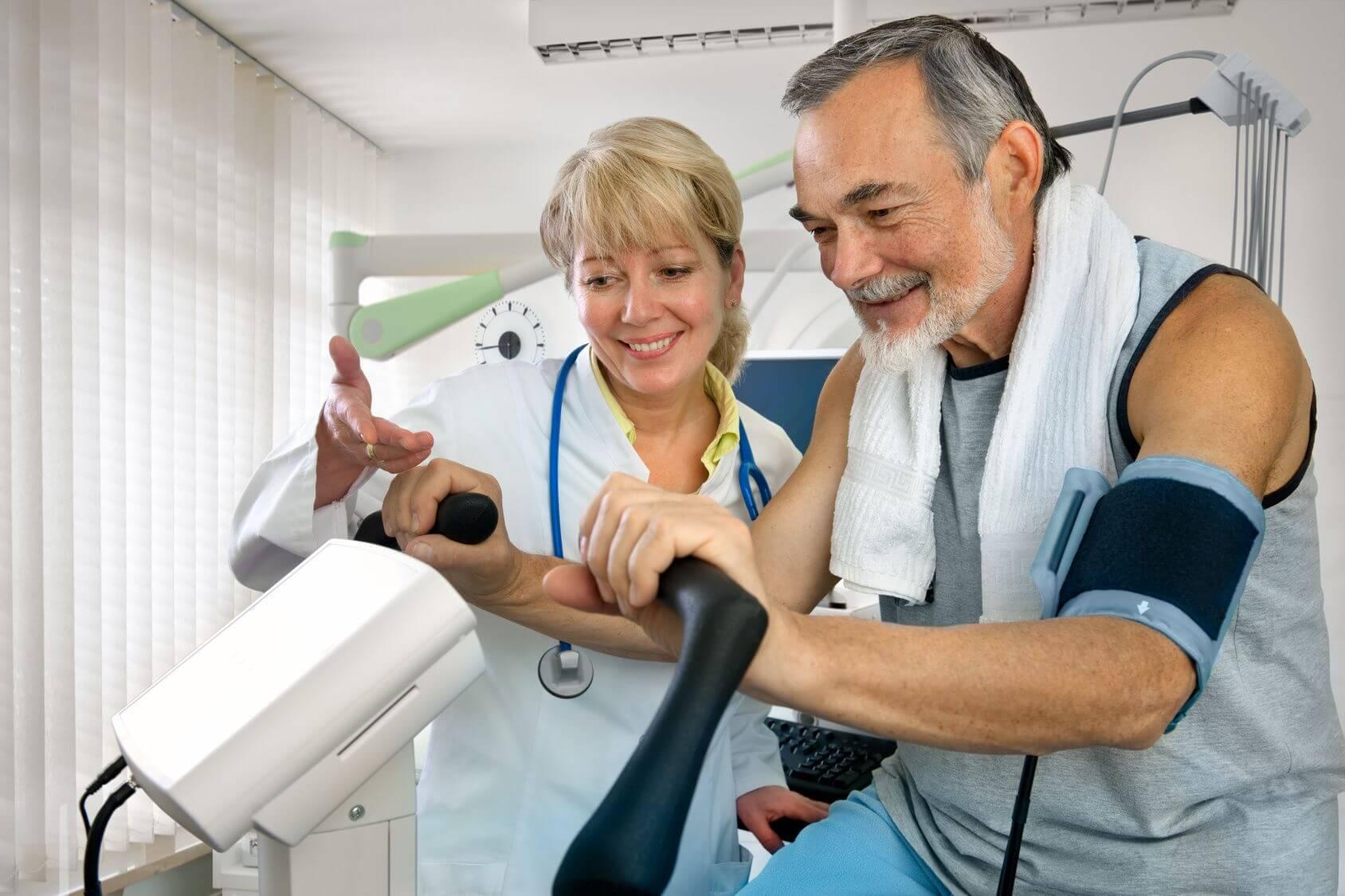 Sport während der Krebstherapie. Mann auf Ergometer mit Ärztin.