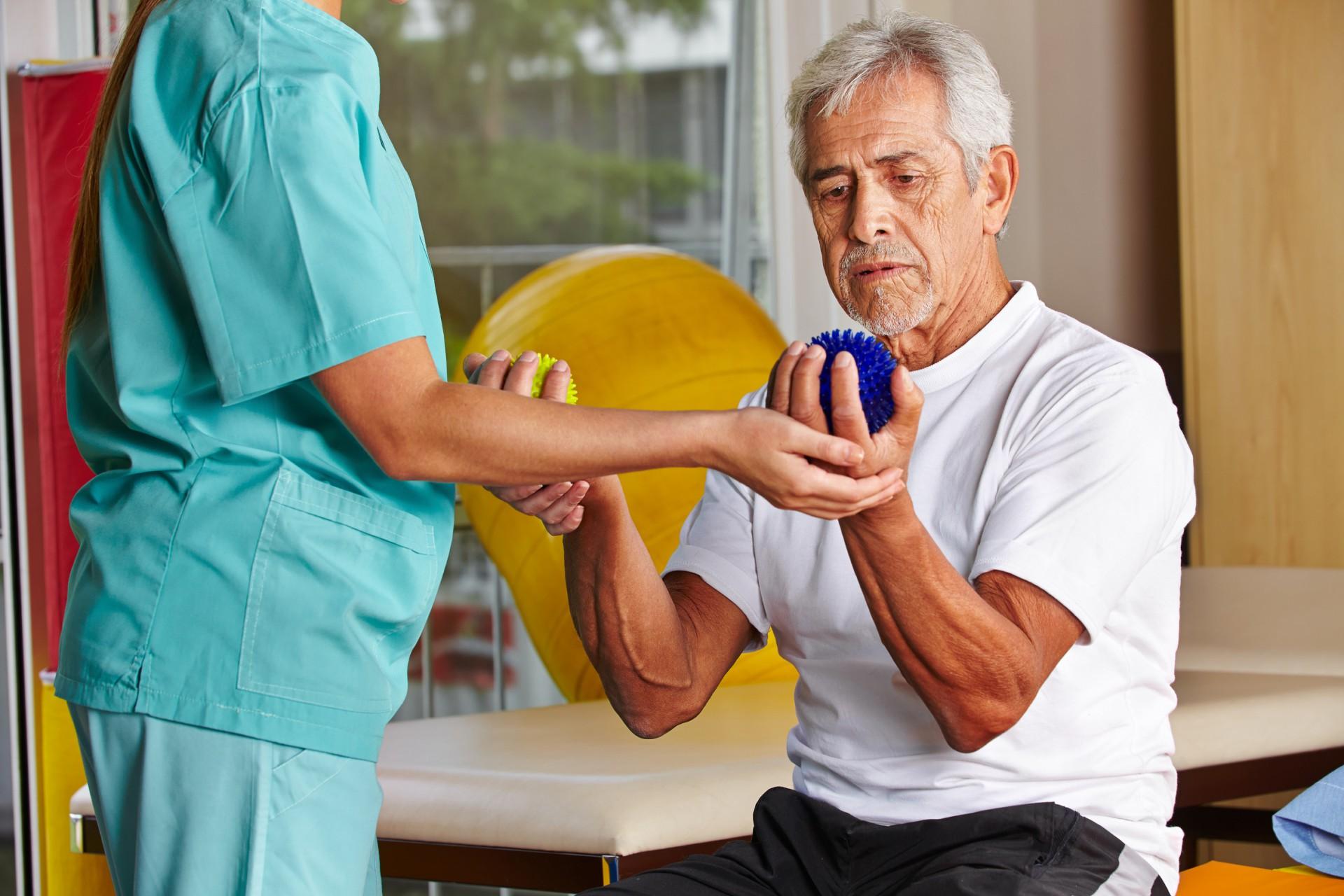 Senior mit Igelball bei der Physiotherapie mit Physiotherapeutin.