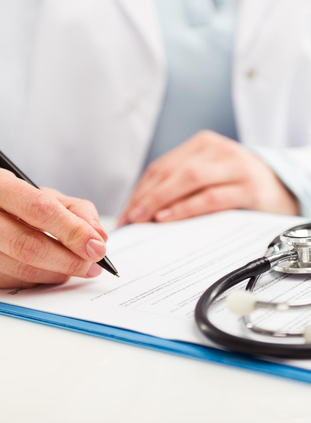 Arzt unterschreibt Papiere.
