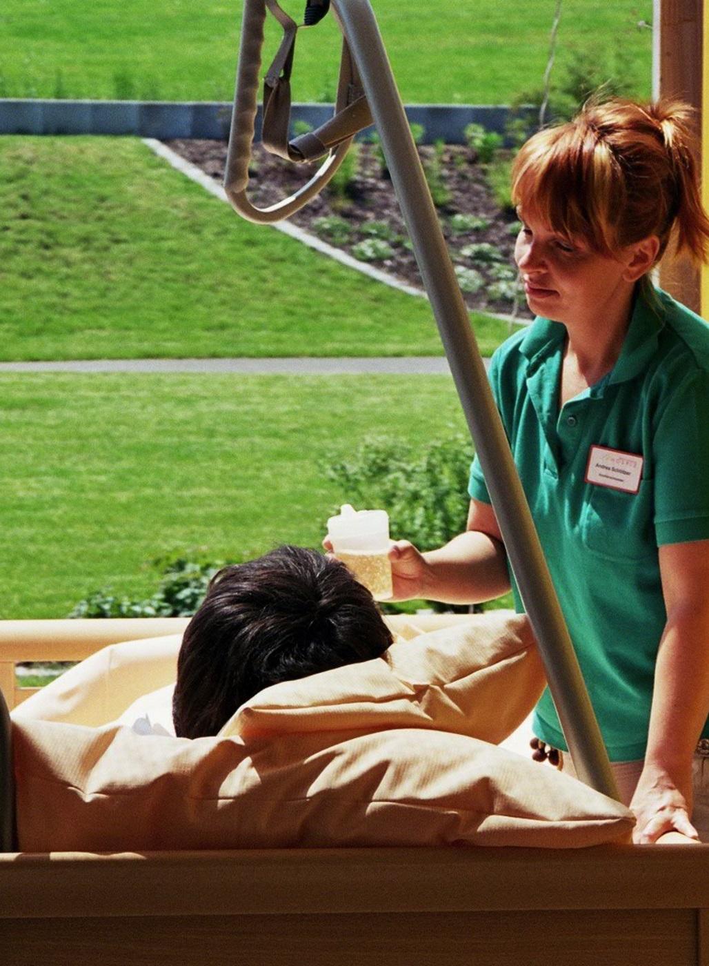 Pflegerin hat Patienten im Bett auf die Terrasse gebracht und reicht ihm ein Getränk.