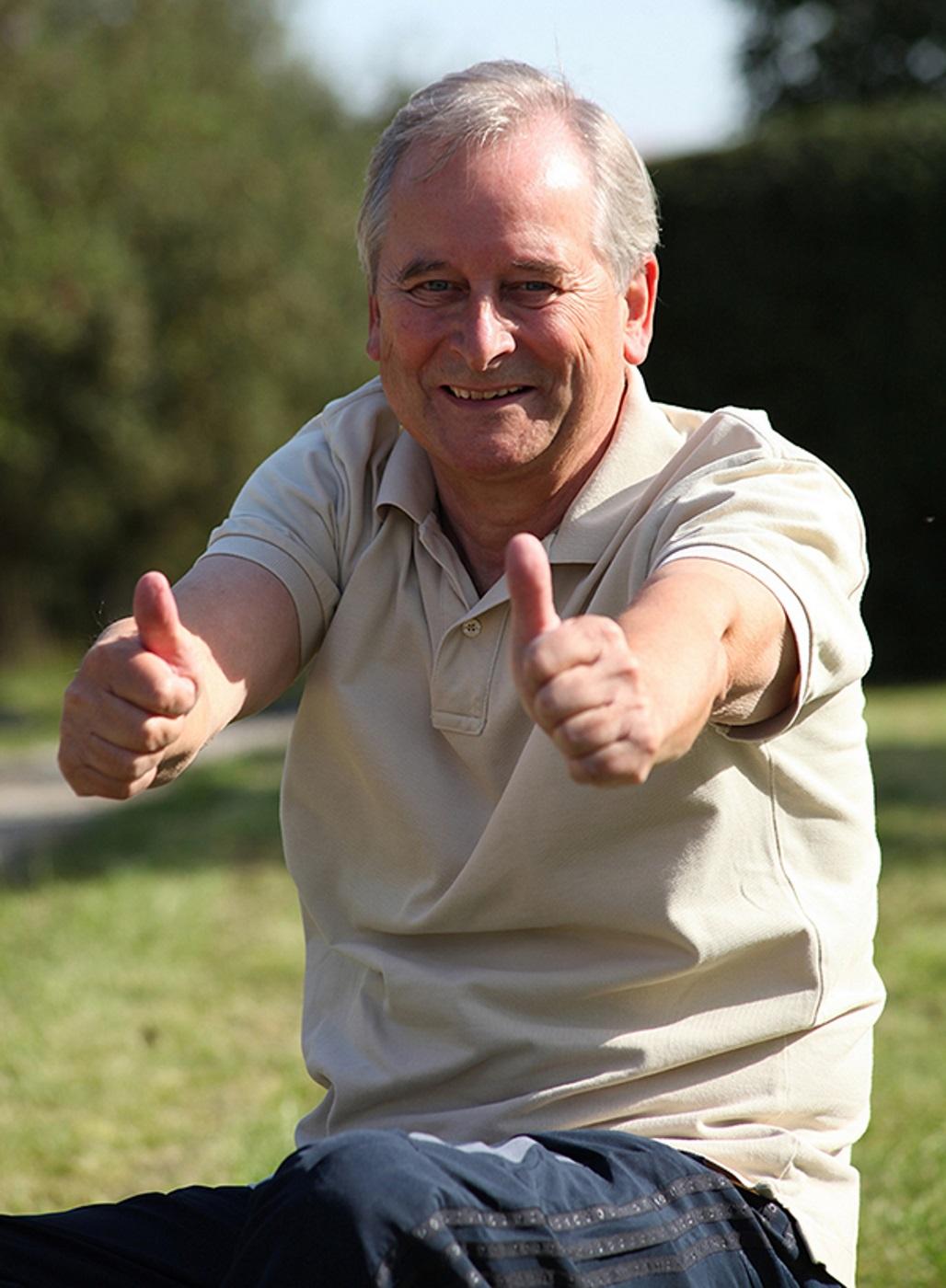 Gesunder, glücklicher älterer Herr zeigt mit beiden Daumen nach oben.