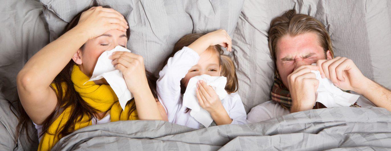 Kranke Familie mit Taschentüchern im Bett.