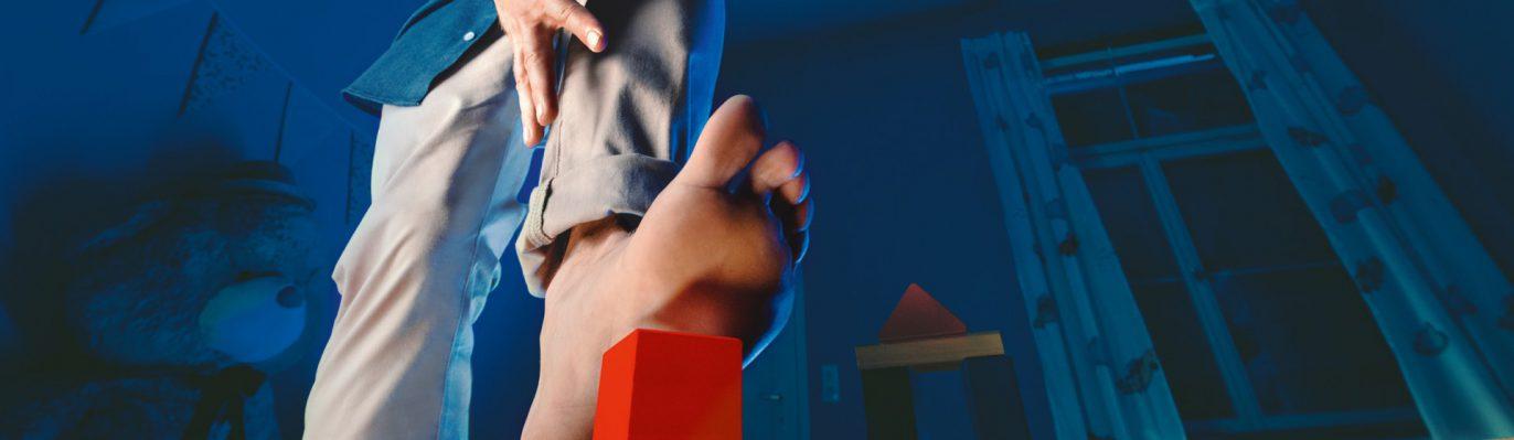 Header zum Thema Masern. Nackter Fuß tritt auf Spielzeug.