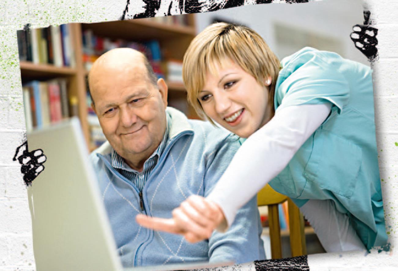 Altenpflegerin zeigt älteren Herren etwas im Internet.