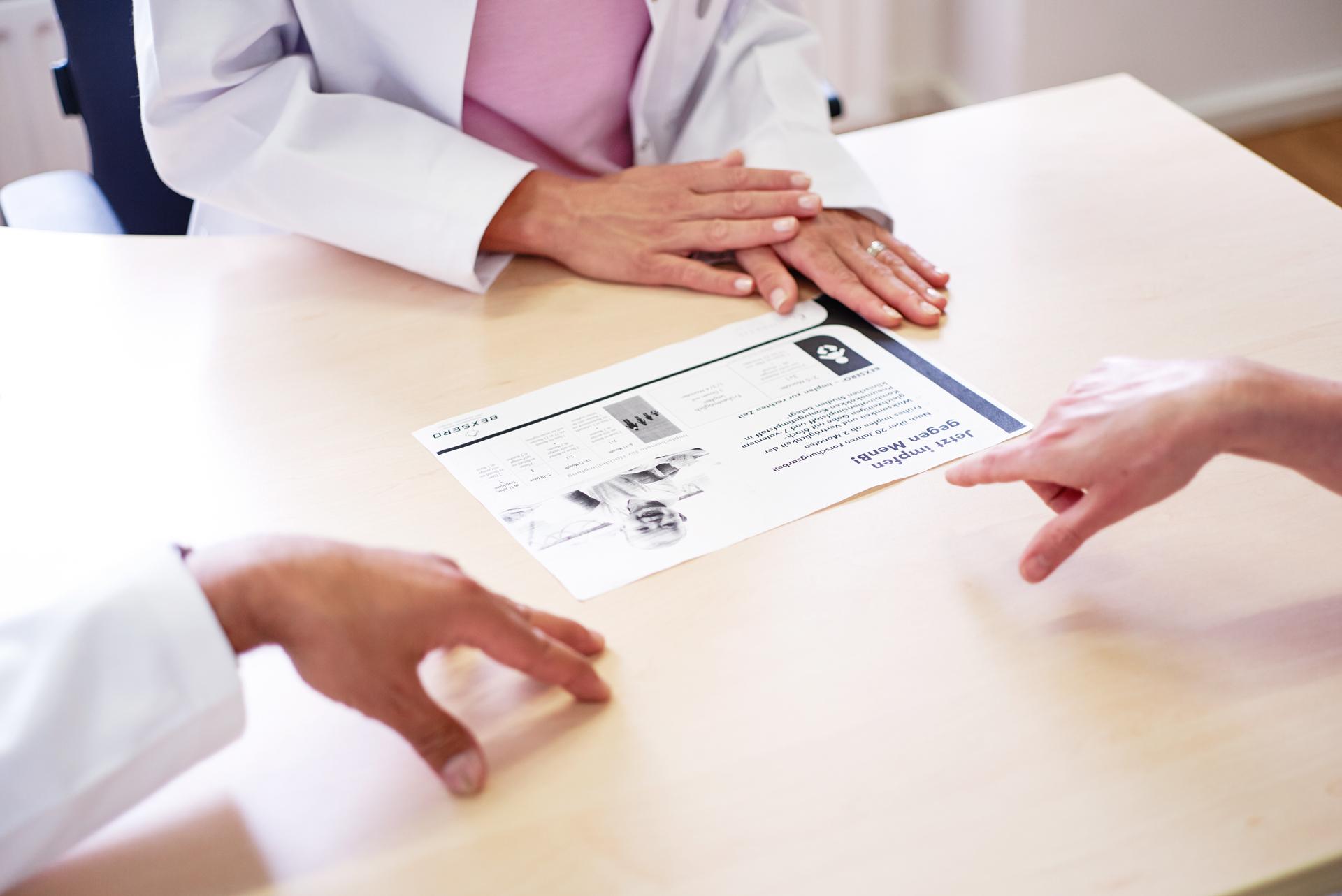 Ärzte besprechen ein Informationsblatt zum Thema Impfungen.