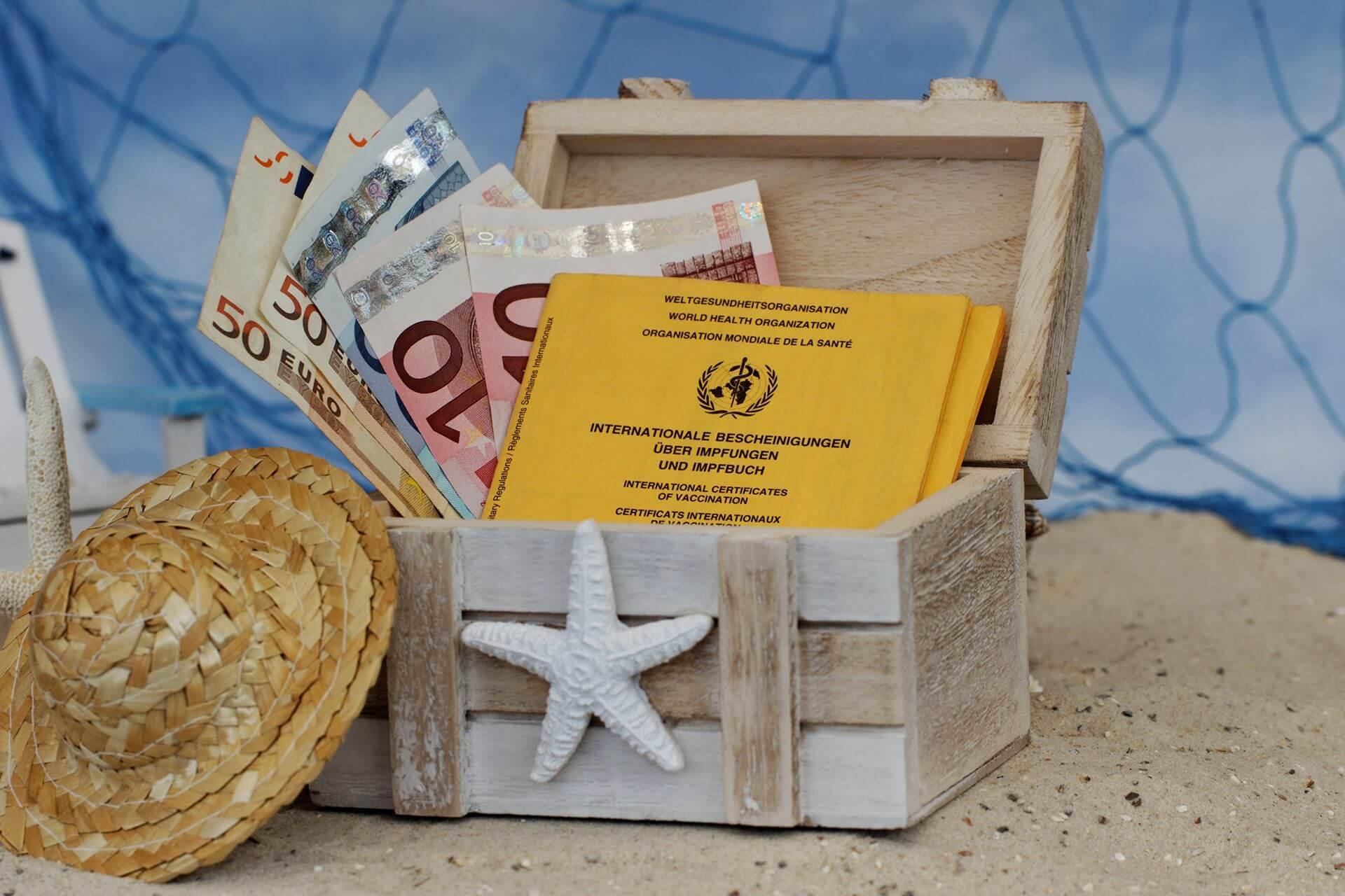 Reisekasse mit Euro-Scheinen und Impfpässen.