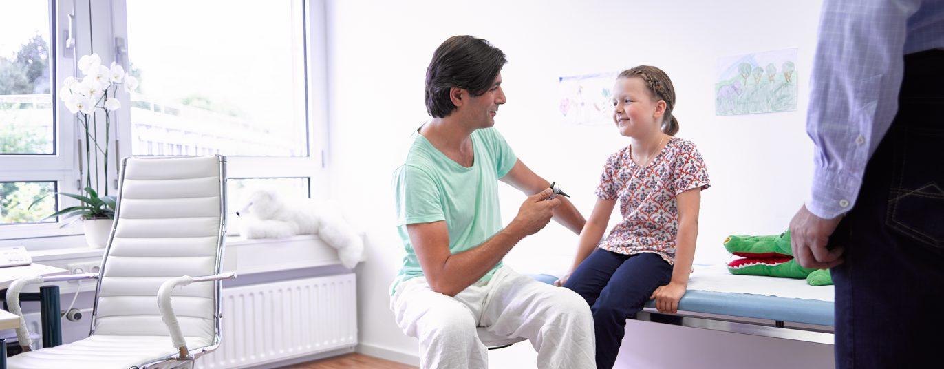 Kinderarzt untersucht junge Patientin.