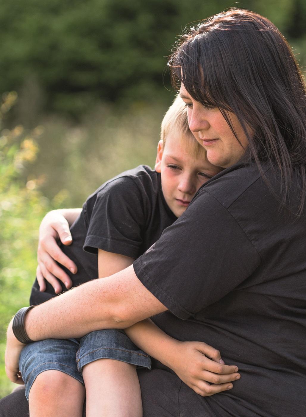 Mutter hält ihren Sohn fest im Arm.