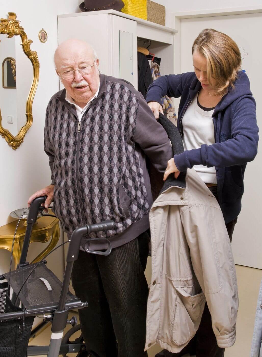 Pflegerin hilft älteren Herren in den Mantel. Foto: Stefan Ernst.
