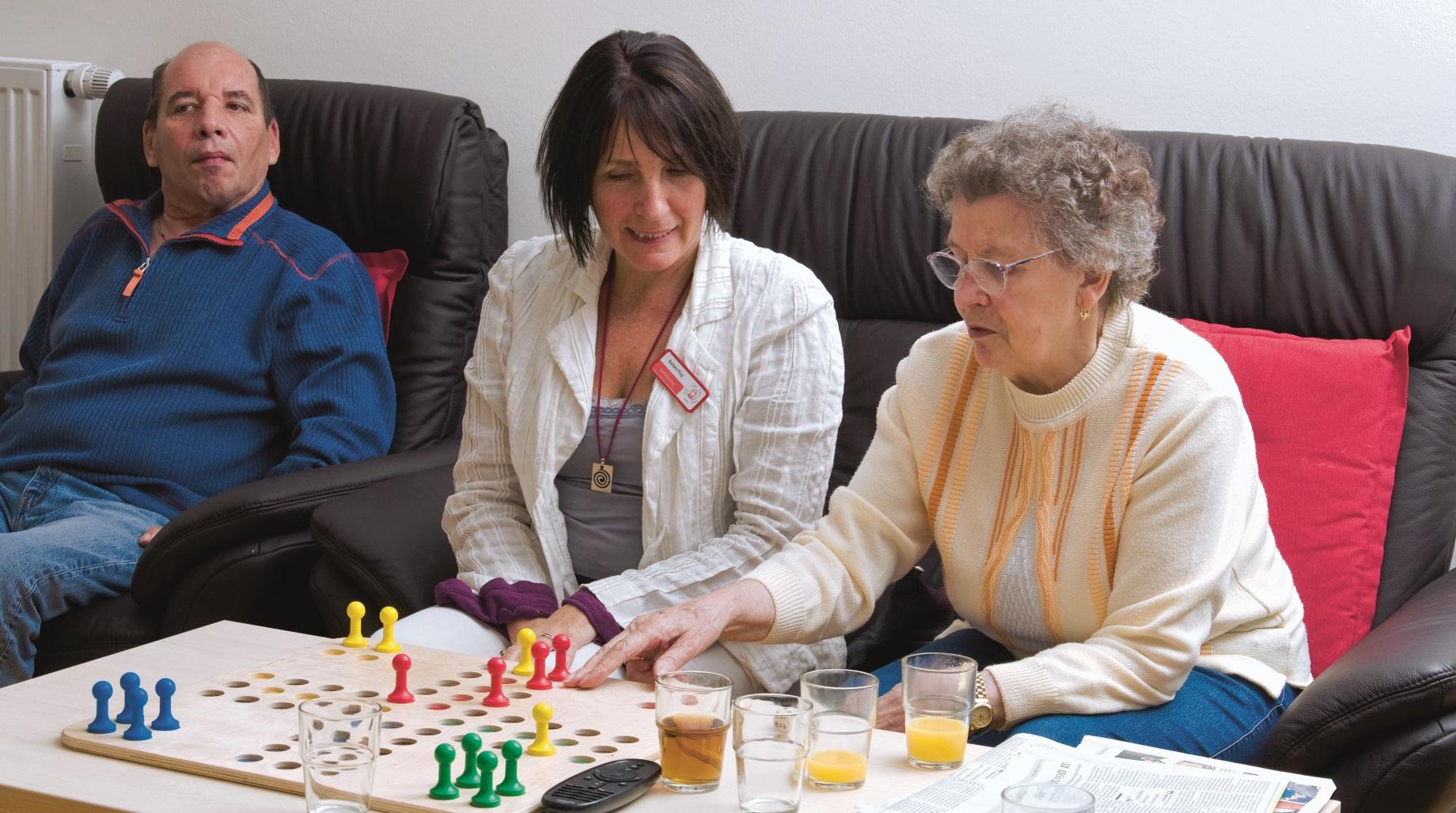 Pflegerin spielt mit älterer Dame Mensch Ärgere Dich Nicht. Foto: Stefan Ernst.