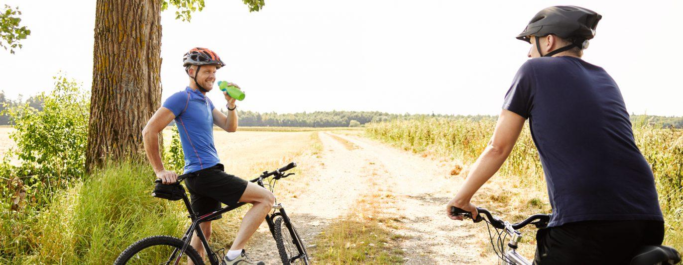 Zwei Männer auf dem Fahrrad in der Landschaft.