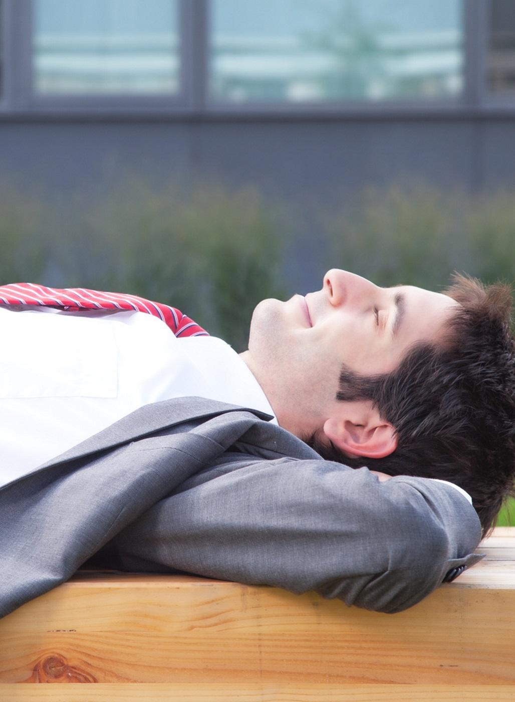 Geschäftsmann entspannt auf einer Bank.