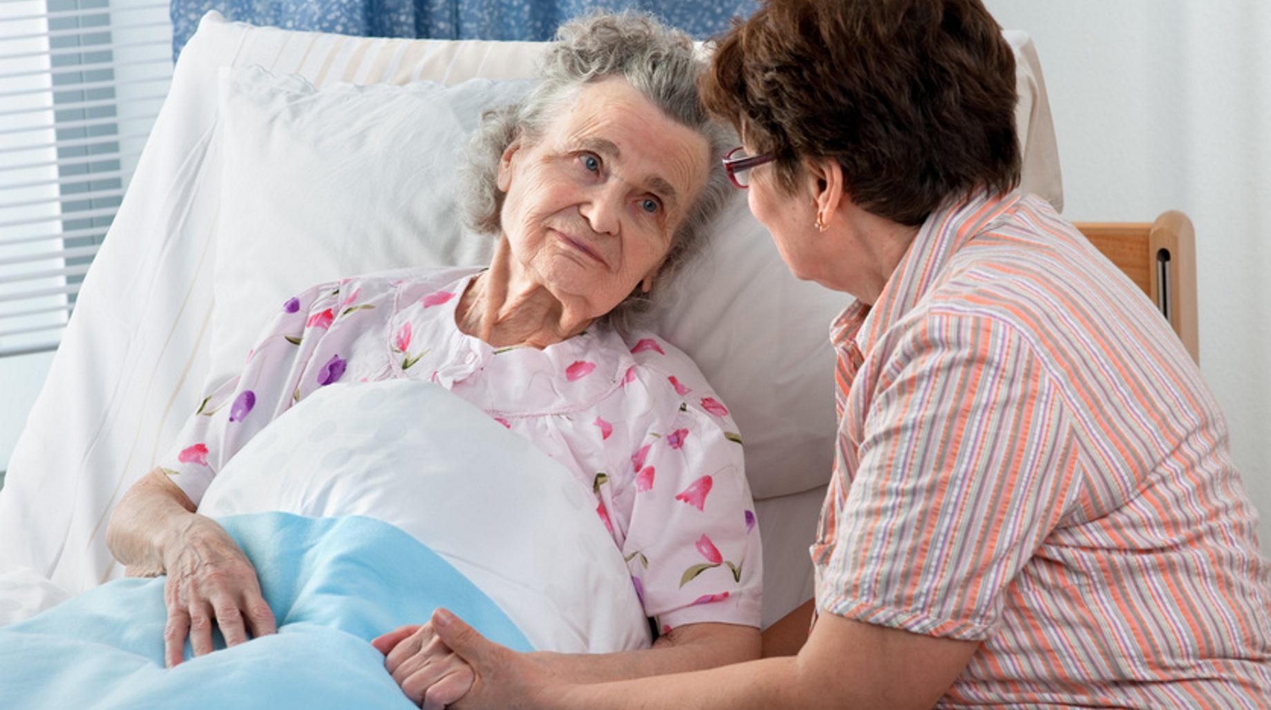 Frau betreut ältere Dame in der Nacht.