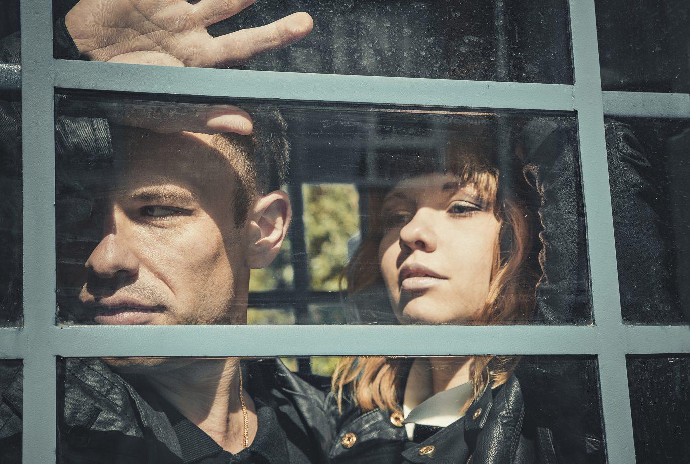 Junges Paar schaut aus Fenster.