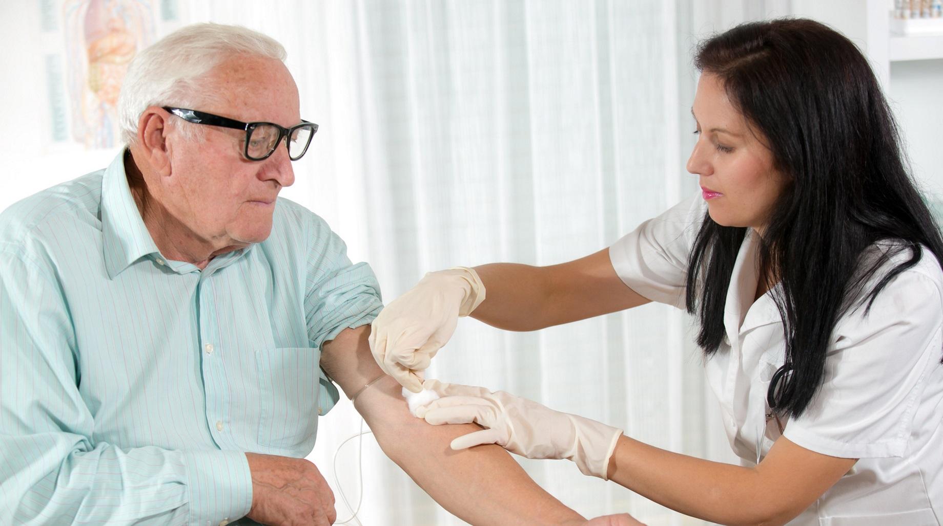 Pflegerin verabreicht älterem Herren eine Spritze.