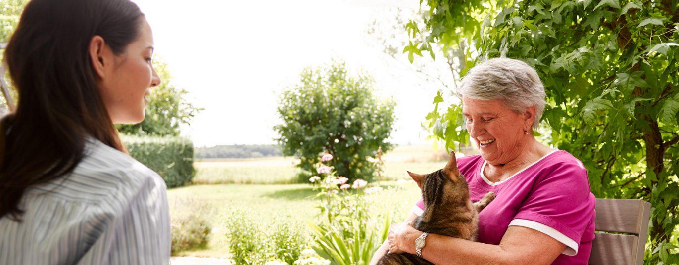 Angehörige mit Seniorin und Katze.