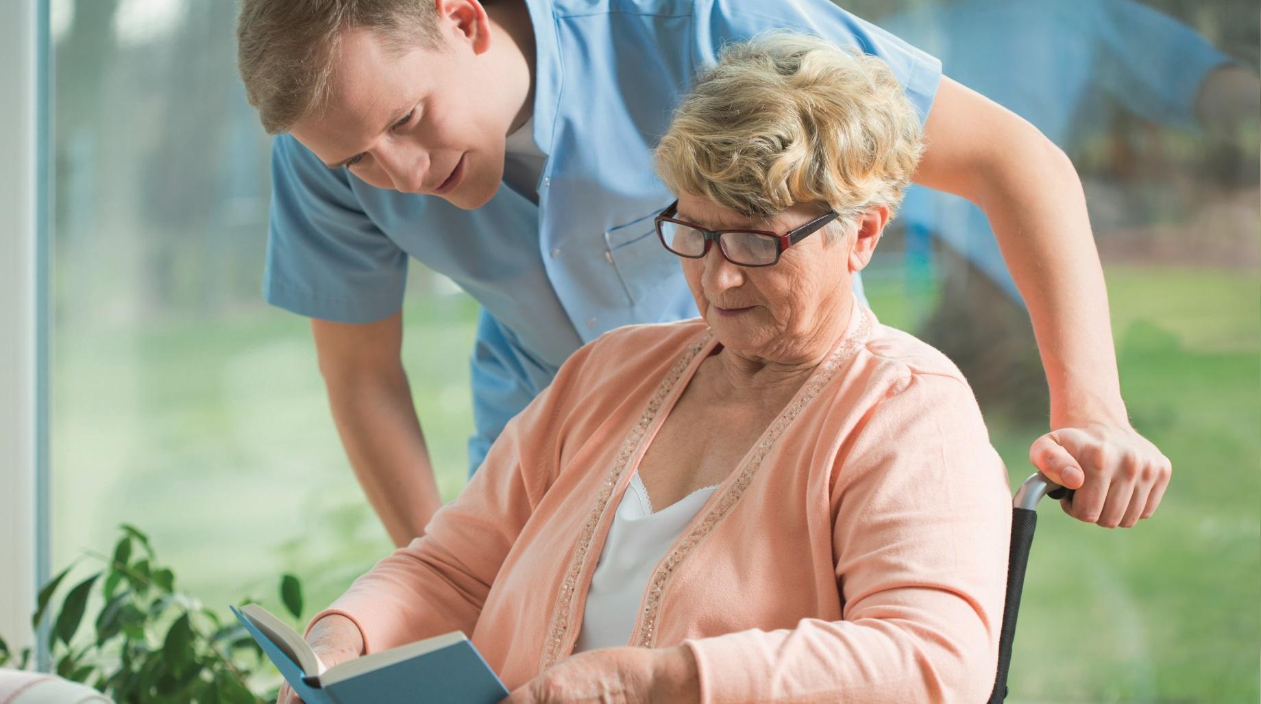 Pflegehilfe unterstützt in den eigenen vier Wänden eine Frau im Rollstuhl.