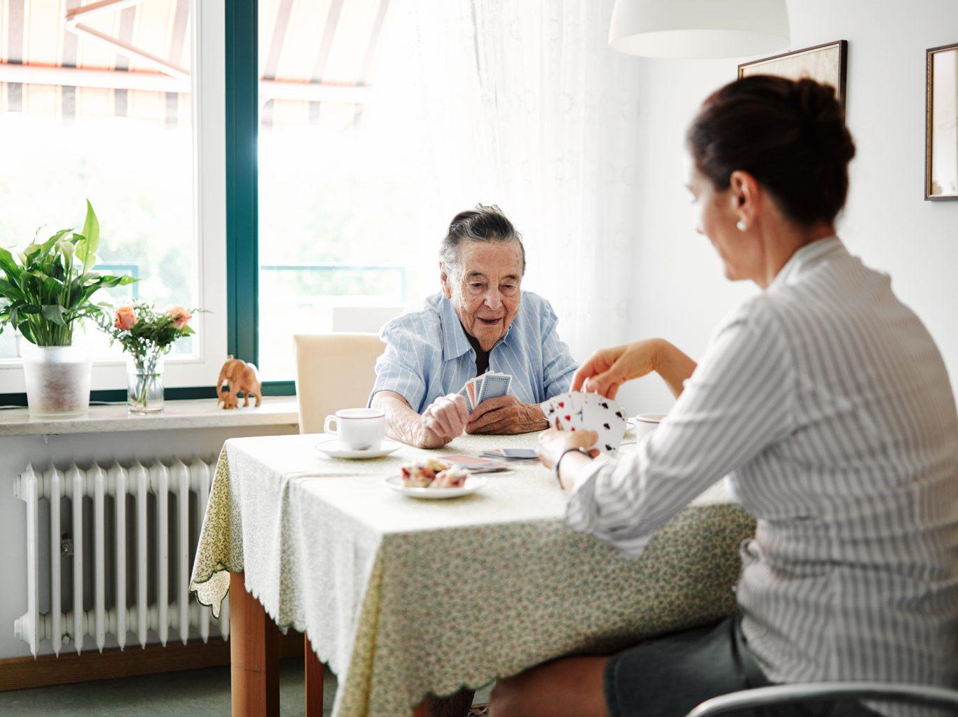 Angehörige spielt Karten mit einer älteren Dame.