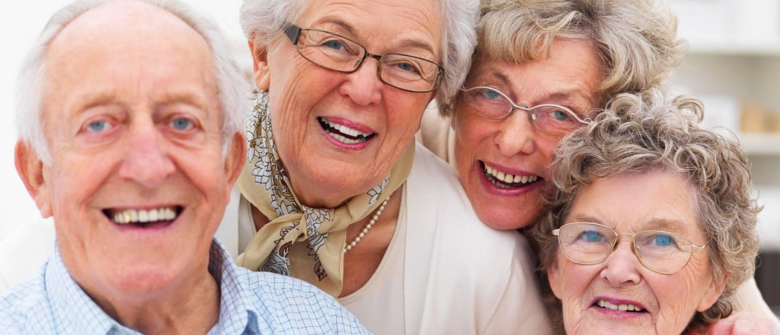 Großaufnahme einer Gruppe von vier Seniorinnen und Senioren, lächelnd