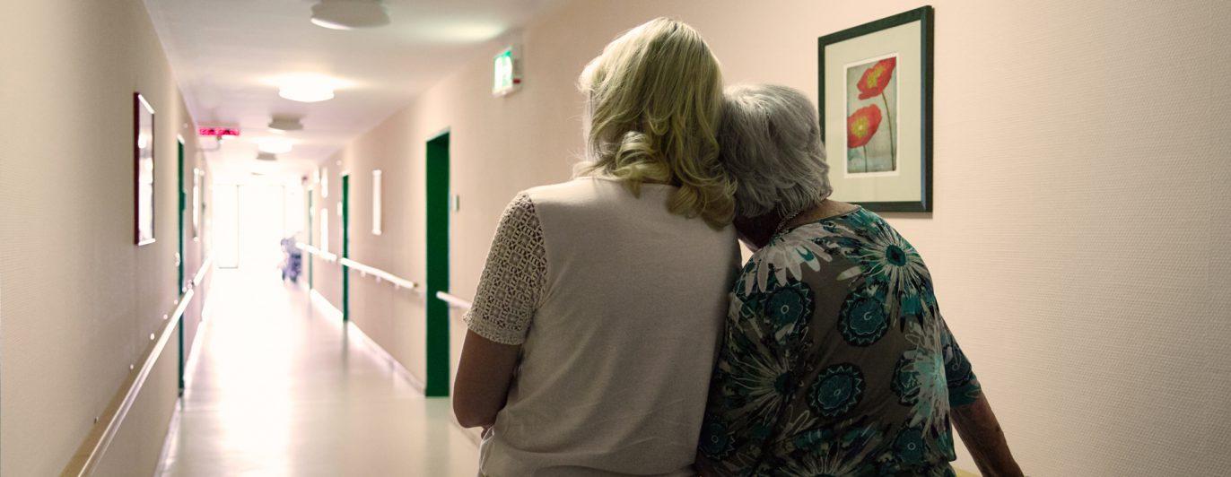 Pflegerin geht mit Patientin über Flur, Kopf auf Schulter.