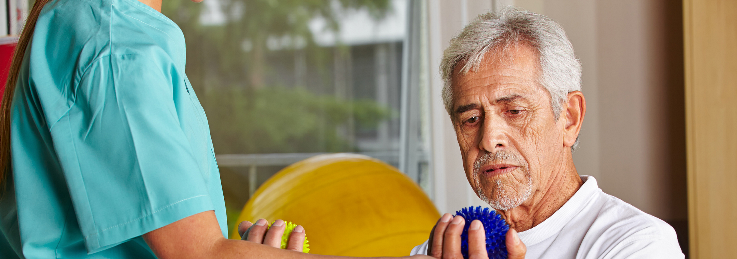 Mann hält bei Rehabilitationstherapie Igelbälle in den Händen.