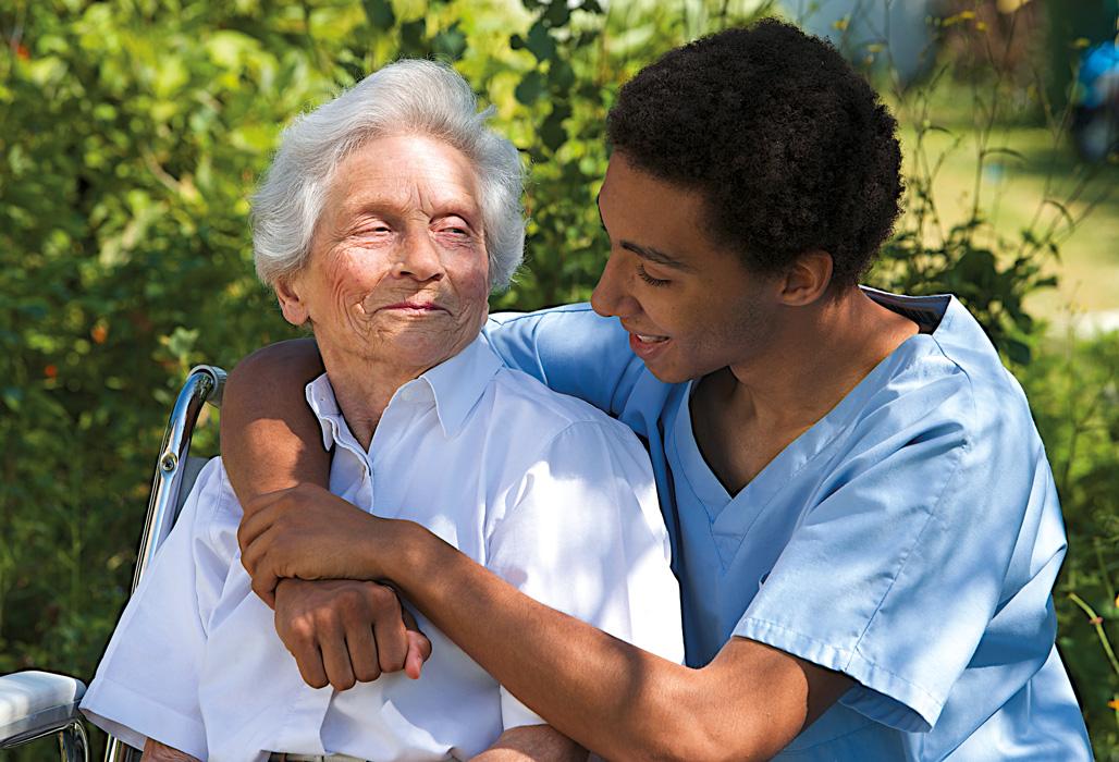 Pfleger in der Ausbildung kümmert sich um eine ältere Person.