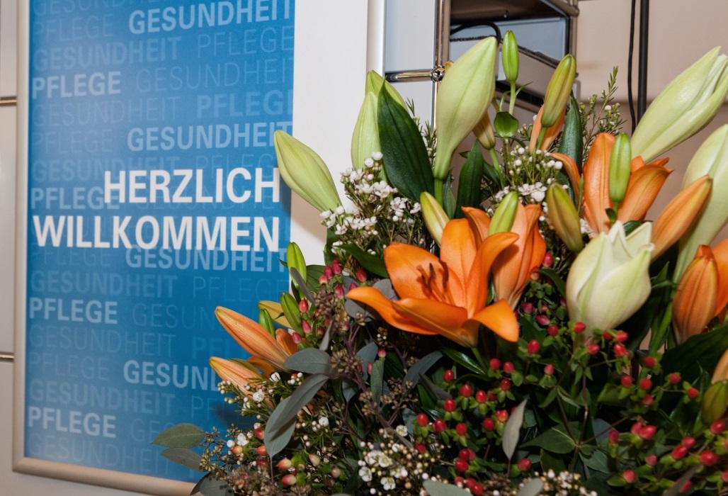 Eingangsbereich einer Veranstaltung, im Vordergrund ein Blumenstrauß.