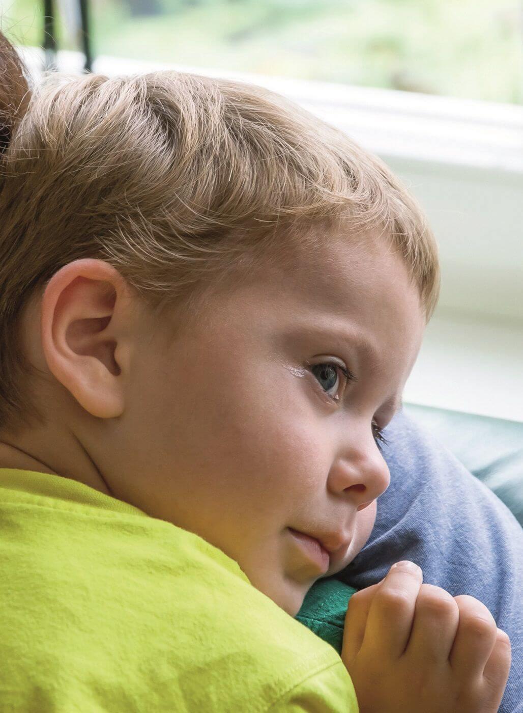 Trauriger Junge auf dem Arm seiner Mutter.