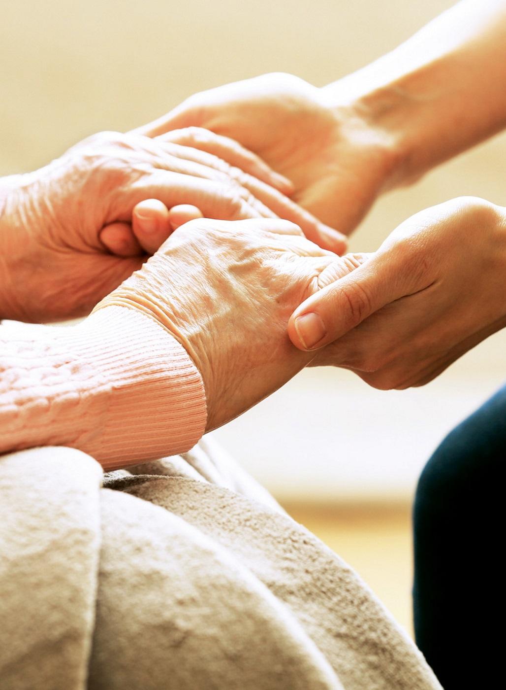 Hände einer jüngeren Frau halten die Hände einer älteren Frau.